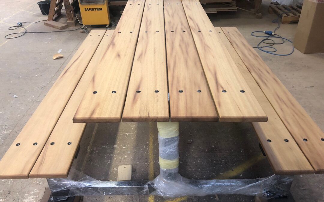 Picnic bench with black powder-coated frame topped with Iroko boards